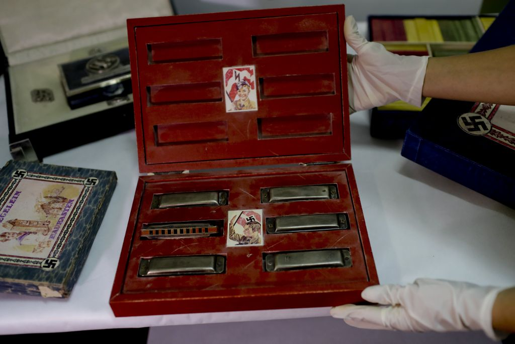 A member of the federal police shows a box with swastikas containing harmonicas for children at the Interpol headquarters in Buenos Aires, Argentina, June 16, 2017. (AP/Natacha Pisarenko)