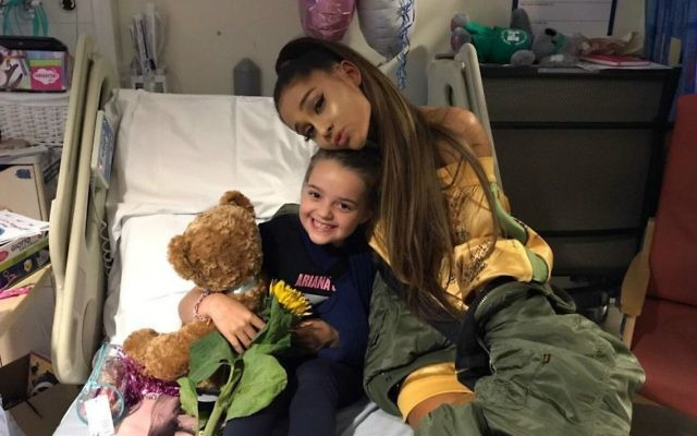 In this photo taken on Friday, June 2, 2017 provided by the Manchester Evening News, victim of the Manchester concert blast Lily Harrison hugs singer Ariana Grande during her visit to the Royal Manchester Children's Hospital, in Manchester, England. (Manchester Evening News via AP)