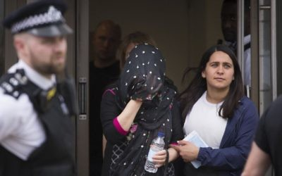 A person (C) is led away at an address in Barking, East London, during a police operation Sunday June 4, 2017, following Saturday night's terrorist incident at London Bridge. (Stefan Rousseau/PA via AP)