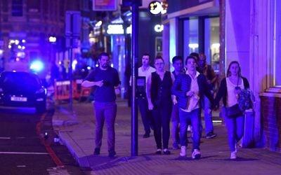 "People run down Borough High Street as police deal with a ""major incident"" at London Bridge in London, June 3, 2017. (Dominic Lipinski/PA via AP)"