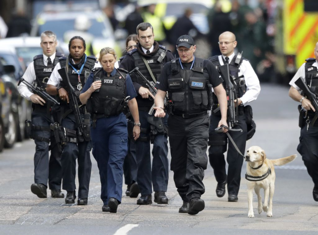 Armed British police officers walk with a detection dog within a cordoned off area after an attack in the London Bridge area of London, Sunday, June 4, 2017.  (AP Photo/Matt Dunham)