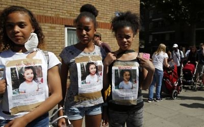 Girls have photos of a missing child on their t-shirts near scene of the massive fire in Grenfell Tower, in rear, in London, Thursday, June 15, 2017. A massive fire raced through the 24-story high-rise apartment building in west London early Wednesday. (AP/Alastair Grant)