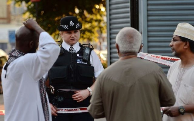 A police officer talks to local people at Finsbury Park in north London, where a vehicle struck pedestrians in north London Monday, June 19, 2017 (Victoria Jones/PA via AP)