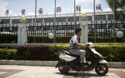 A man rides a motorbike outside of a Huajian Group shoe factory in Ganzhou in southeastern China's Jiangxi Province, Tuesday, June 6, 2017. (AP/Mark Schiefelbein)