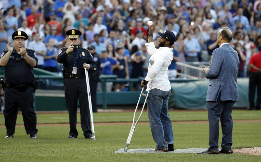 Injured Capitol Hill Police officer David Bailey throws out a ceremonial first pitch with Joe Torre, MLB's Chief Baseball Officer before the annual congressional baseball game, June 15, 2017. (AP Photo/Alex Brandon)