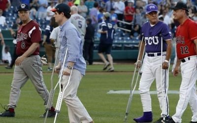 Injured aide Zach Barth (L) and Republican Congressman Roger Williams walk off the field before the annual congressional baseball game in Washington, DC, June 15, 2017. (AP Photo/Alex Brandon)