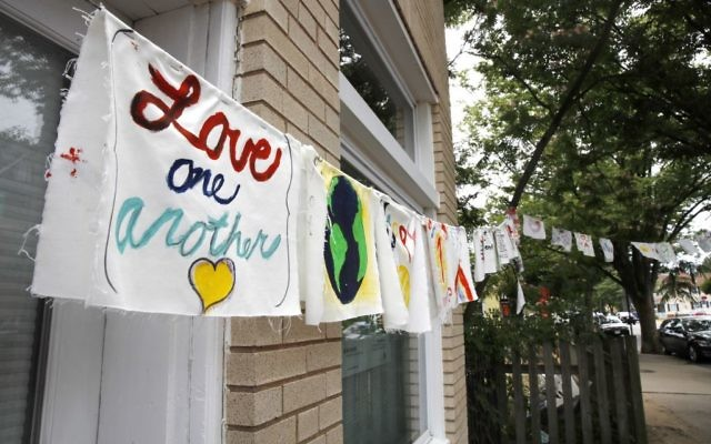 Painted cloth flags including one saying 'Love One Another' are strung across a store in Virginia on June 15, 2017, a day after Congressman Steve Scalise was shot during nearby during baseball practice. (AP Photo/Jacquelyn Martin)