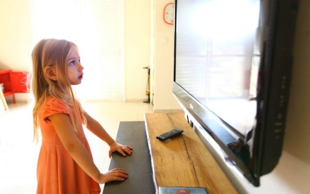 A young girl staring at a TV. (illustrative photo: Chen Leopold/Flash90)