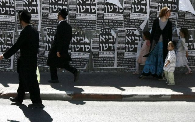 Illustrative: Ultra-Orthodox boys and a family walk past a poster that says the internet brings cancer in Jerusalem, July 2, 2009. (Rishwanth Jayapaul/Flash90)