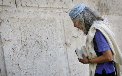 Religious Jewish women which are part of the Women of the Wall organization wear tfillin (prayer shawls) and tallit as they read from the Torah and pray at Robinson's Arch,  near the Western Wall in Jerusalem. The WOW organizes women's prayer groups at the Western Wall at the start of every new Jewish month (Rosh Hodesh). Jewish ultra orthodox communities oppose women's singing in the presence of men, reading from the Torah, and wearing the ritual garments and objects traditionally associated with men. March 12, 2013. Photo by Miriam Alster/FLASH90