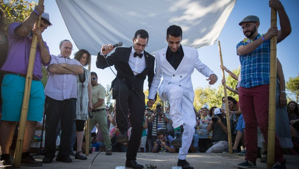 A gay couple has a symbolic wedding ceremony under a traditional wedding canopy during the annual Pride parade in Jerusalem, July 21, 2016. (Hadas Parush/Flash90)