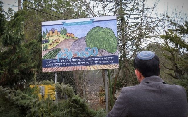 A man looks at a sign for the 50th anniversary celebrations of Kfar Etzion at the entrance to Kfar Etzion, in the West Bank on January 30, 2017. (Gershon Elinson/Flash90)
