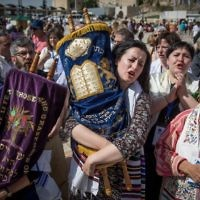 Members of the Reform and Conservative Jewish movements hold torah scrolls during mixed men and women's prayer at the public square in front of the Western Wall, in Jerusalem's Old City, on May 18, 2017. (Yonatan Sindel/Flash90)