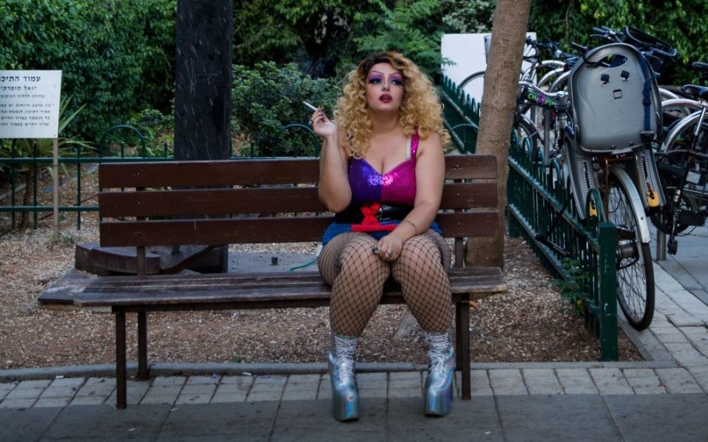 A performer at the 'Wigstock Drag Queen Show' smokes a cigarette before the show at Meir Park, in Tel Aviv, as part of Gay Pride Week, on Wednesday, June 7, 2017 (Miriam Alster/FLASH90)