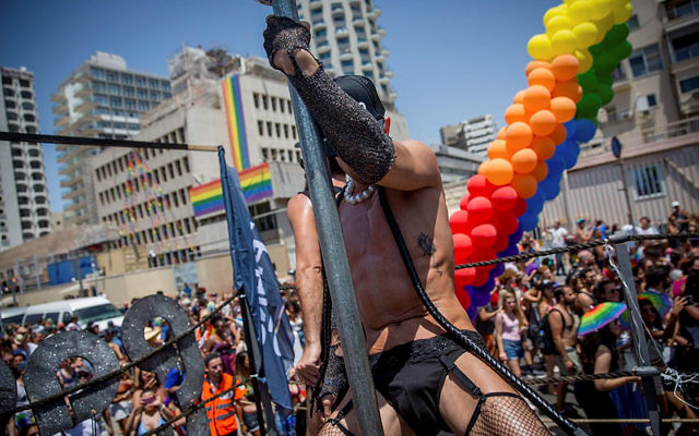 A man wearing fishnet tights dances at the annual Gay Pride Parade in Tel Aviv, on June 9, 2017. Friday's Parade marks the end of Pride Week in Tel Aviv, internationally acclaimed as one of the most proud and gay-friendly cities in the world. (Miriam Alster/Flash90)