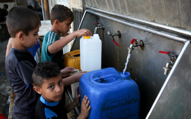 Palestinian children fill jerrycans with drinking water from public taps in the southern Gaza Strip, June 11, 2017. (Abed Rahim Khatib/ Flash90)