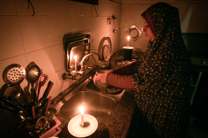 A Palestinian woman washes dishes by candlelight at her makeshift home in the Rafah refugee camp, in the southern Gaza Strip on June 12, 2017. (Abed Rahim Khatib/Flash90)