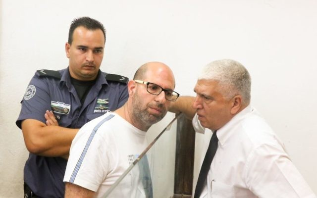 Illustrative: Shaul Shamai (c), suspected of molesting his students while acting as a substitute teacher, arrives escorted by prison guards at the Tel Aviv Magistrate's Court, June 13, 2017. (Flash90)