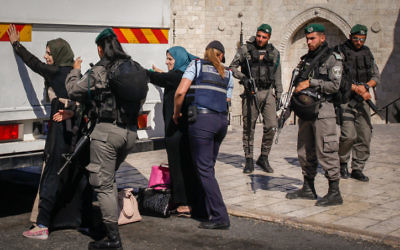Israeli security forces check Palestinian women in front of the Damascus Gate in Jerusalem's Old City before allowing them to board a bus that will take them back to the West Bank on June 17, 2017. (Sliman Khader/Flash90)