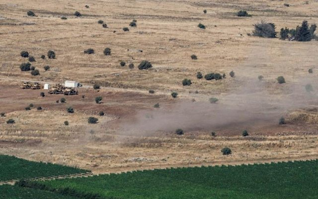 Smoke seen rising from a field on the Israeli side of the Israeli-Syrian border in the Golan Heights on June 24, 2017. (Basel Awidat/Flash90)