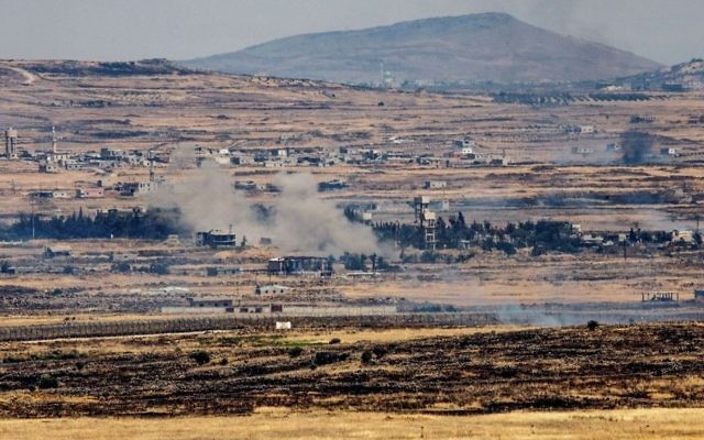 A picture taken from the Israeli side of the Israeli-Syrian border shows smoke rising near the border in the Golan Heights, during fights between rebels and the Syrian army on June 25, 2017. (Basel Awidat/ Flash90)