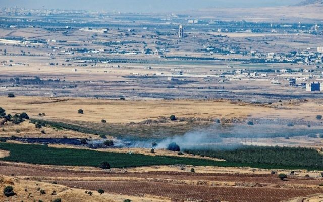 A picture taken from the Israeli side of the border shows smoke rising near the Israeli-Syrian border in the Golan Heights during fights between the rebels and the Syrian army on June 25, 2017. (Basel Awidat/Flash90)