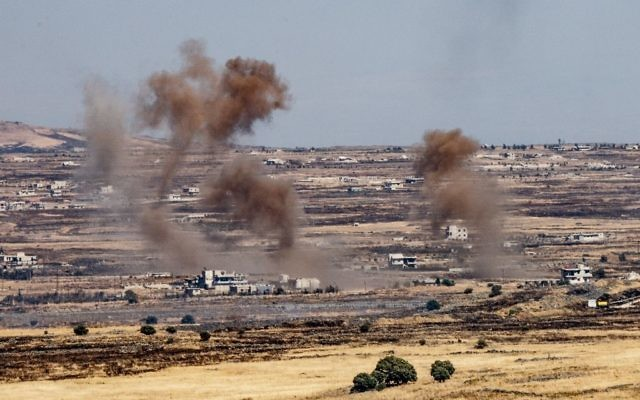A picture taken from the Israeli side of the border shows smoke rising near the Israeli-Syrian border on the Golan Heights during fights between the rebels and the Syrian army inside Syria, June 25, 2017. (Basel Awidat/Flash90)