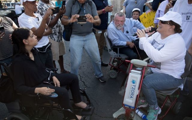 MK's Karin Elharar (L) and Ilan Gillon (2R) at a protest calling to increase disability stipends outside the Prime Minister's Residence in Jerusalem, June 27, 2017. (Yonatan Sindel/Flash90)