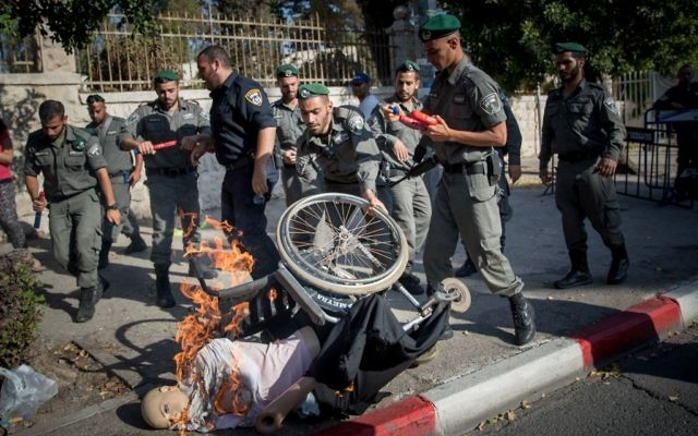 Activists set fire to a doll in a wheelchair at a protest calling to increase disability stipends outside the Prime Minister's Residence in Jerusalem, June 27, 2017. (Yonatan Sindel/Flash90)