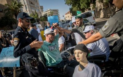 An activist tries to set himself on fire at a protest calling to increase disability stipends outside the Prime Minister's Residence in Jerusalem, June 27, 2017. (Yonatan Sindel/Flash90)