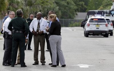 Authorities confer near the scene of a shooting where they said there were multiple fatalities in an industrial area near Orlando, Florida, June 5, 2017. (AP/John Raoux)