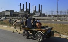 In this  June 4, 2017, photo, a father and his children ride their donkey cart past the idled Gaza power plant at Nusseirat, in the central Gaza Strip (AP Photo/Adel Hana)
