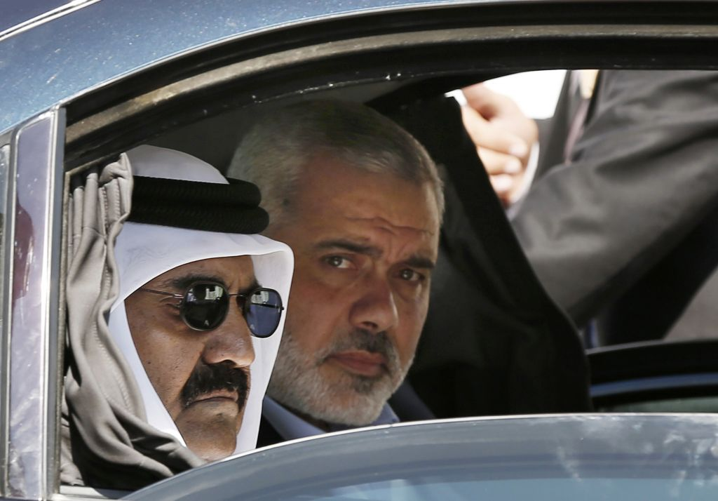 In this Oct. 23, 2012 photo, then-Emir of Qatar Sheikh Hamad bin Khalifa al-Thani, left, and Gaza's Hamas prime minister Ismail Haniyeh, arrive for a corner-stone laying ceremony for Hamad, a new residential neighborhood in Khan Younis, southern Gaza Strip. (AP Photo/Mohammed Salem, Pool)