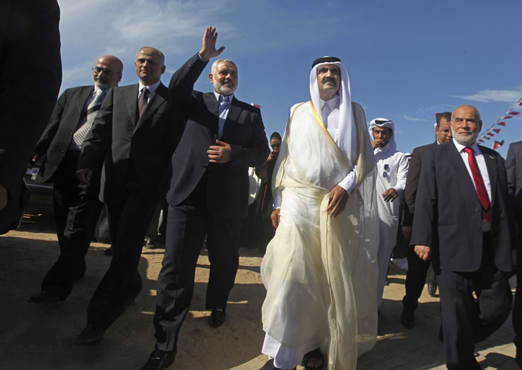 In this Oct. 23, 2012 photo, then-Emir of Qatar Sheik Hamad bin Khalifa al-Thani, center right, and then Gaza's Hamas Prime minister Ismail Haniyeh, third left, arrive for the corner-stone laying ceremony of a new center providing artificial limbs, in Bait Lahiya, northern Gaza Strip. (AP Photo/Ali Ali, Pool)