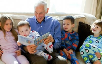 Harold Grinspoon, the founder of PJ Library, reads one of the program's books with a gaggle of children. (PJ Library)