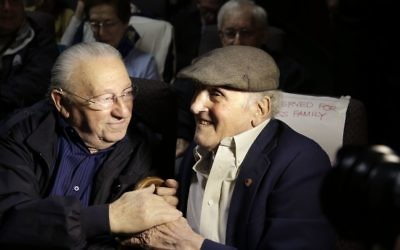 """In this Wednesday, June 7, 2017 photo, Holocaust survivors Israel Arbeiter, left, and Steve Ross, right, greet one another at a theater before the premier of the film """"Etched in Glass: The Legacy of Steve Ross,"""" in West Newton, Mass. (AP Photo/Steven Senne)"""