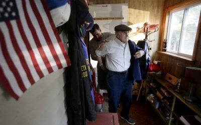 """In this Wednesday, June 7, 2017, photo, Holocaust survivor Steve Ross, right, is helped with his jacket by his son Mike Ross, behind, as they prepare to depart Steven Ross' home in Newton, Mass., to attend the premier of the film """"Etched in Glass: The Legacy of Steve Ross."""" (AP Photo/Steven Senne)"""