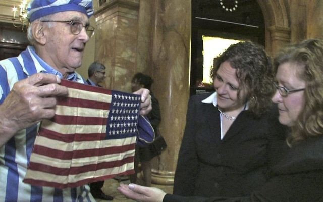 """In this Nov. 11, 2012, still image from the film """"Etched in Glass: The Legacy of Steve Ross,"""" provided by Many Hats Productions, Holocaust survivor Steve Ross, from left, displays an American flag to Brenda Sattler and Gwen Sattler Allanson at a Veteran's Day event at the Statehouse in Boston. (Tony Bennis/Many Hats Productions via AP)"""
