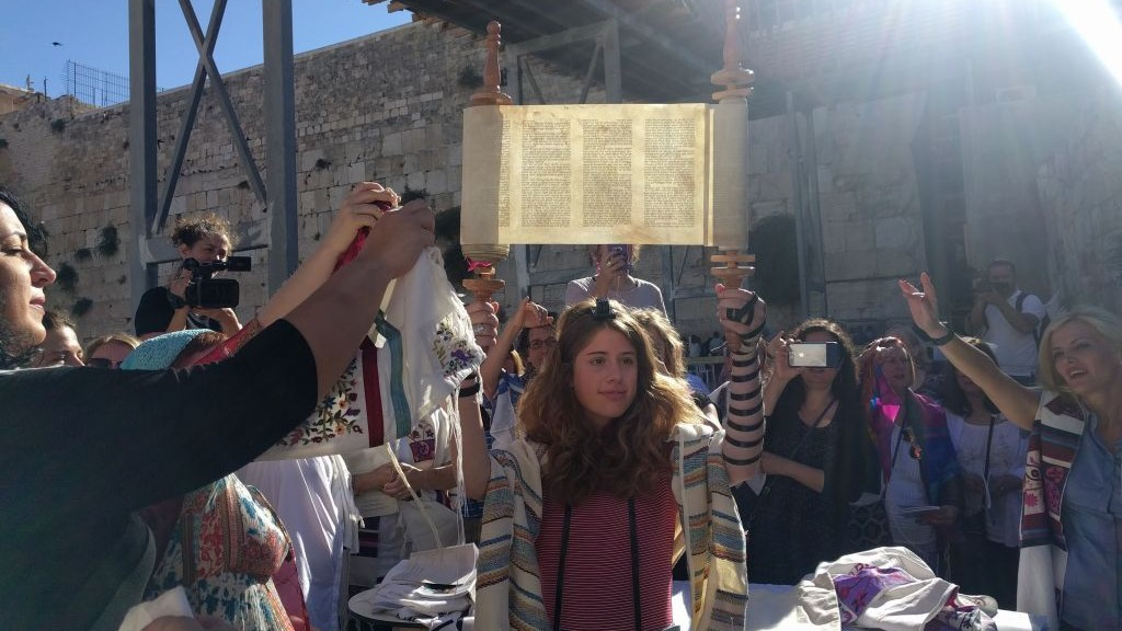 A young member of Women of the Wall holds up the miniature Torah scroll during the monthly Rosh Hodesh service on June 25, 2017, in the women's section of the Western Wall plaza, just before Netanyahu froze the Kotel Agreement. (Melanie Lidman/Times of Israel)