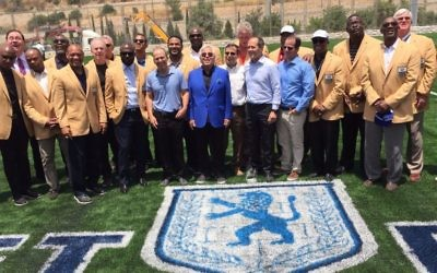 New England Patriots owner and philanthropist Robert Kraft (center, blue blazer) with most of the 18 NFL 'Gold Jackets' currently in Israel and at the ribbon-cutting ceremony of the new Kraft Family Sports campus in Jerusalem (Jessica Steinberg/Times of Israel)