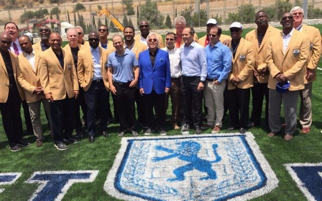 New England Patriots owner and philanthropist Robert Kraft (center, blue blazer) with most of the 18 NFL 'Gold Jackets' in Israel and at the ribbon-cutting ceremony in June, 2017 for Israel's first full-size American football field, part of the new Kraft Family Sports campus in Jerusalem (Jessica Steinberg/Times of Israel)