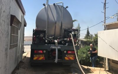 Migdalim settlement director Yael Hashash looks on as a tanker fills the settlements water tower on June 4, 2016. (Jacob Magid/Times of Israel)