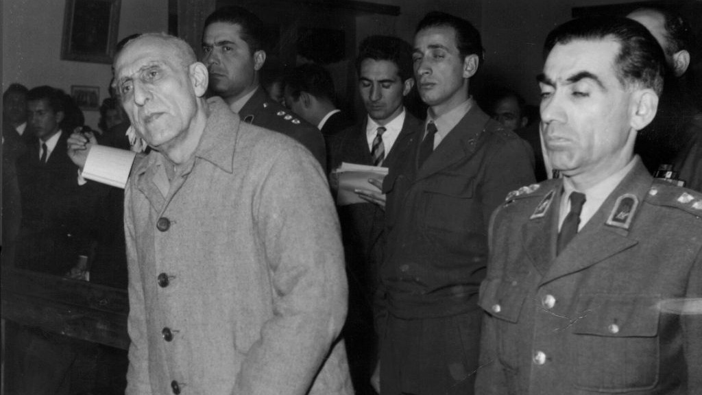 In this Dec. 21, 1953 file photo, former Iranian PM Mohammed Mosaddegh, left, is sentenced to three years solitary confinement by a military court after findidng him guilty on 13 charges of acting against the Shah, in Tehran, Iran. (AP Photo, File)