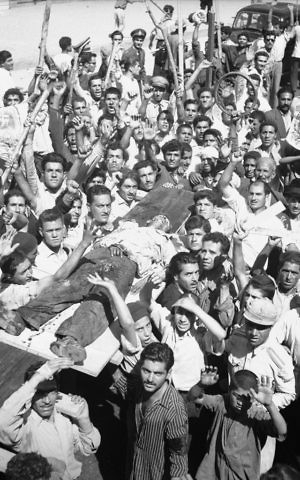 In this Aug. 19, 1953 file photo, the body of a man killed in a pro-Shah riot which swept through Tehran is carried aloft by demonstrators. (AP Photo/Aziz Rashki, File)