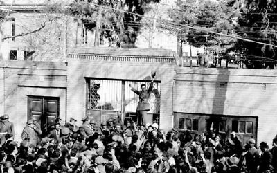 In this Feb. 28, 1953 file photo, an army officer rallies a crowd of supporters of Shah Mohammed Reza Pahlevi in front of the home of then Iranian PM Mohammed Mossadegh as riots broke out in Tehran. (AP Photo, File)