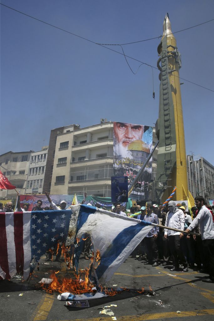 Iranian protesters burn representations of US and Israeli flags in their annual pro-Palestinian rally marking Al-Quds (Jerusalem) Day, as a Ghadr H surface-to-surface ballistic missile is displayed by Revolutionary Guard, in Tehran, Iran, Friday, June 23, 2017. A portrait of the late Iranian revolutionary founder Ayatollah Khomeini and Jerusalem's Dome of Rock hangs from a building in background. (AP Photo/Vahid Salemi)