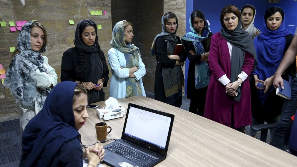 In this Sunday, May 22, 2017, photo, staffers of the Bamilo online shopping site attend a meeting at their office in Tehran, Iran. (AP Photo/Ebrahim Noroozi)