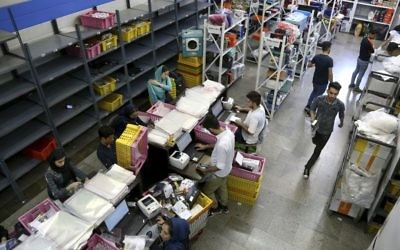 In this Sunday, May 22, 2017, photo, staffers work at the fulfillment center of the Bamilo online shopping site in Tehran, Iran. (AP Photo/Ebrahim Noroozi)