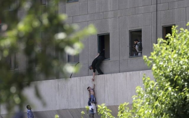 A man hands a child to a security guard from Iran's parliament building after an assault of several attackers, in Tehran, Iran, June 7, 2017 (Fars News Agency, Omid Vahabzadeh via AP)