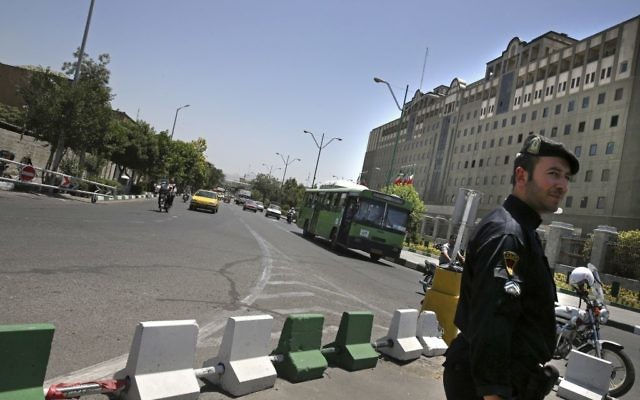 A police officer stands guard as vehicles drive in front of Iran's parliament building in Tehran, Iran, Thursday, May 8, 2017.  (AP/Vahid Salemi)